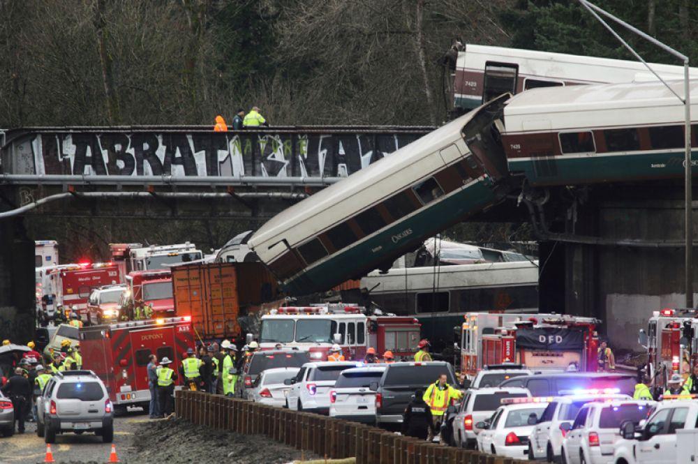 На месте аварии поезда Amtrak, последний вагон которого на скорости 130 километров в час сошел с рельс, рухнул с моста на шоссе и задел несколько автомобилей, штат Вашингтон, США. 18 декабря 2017 года.
