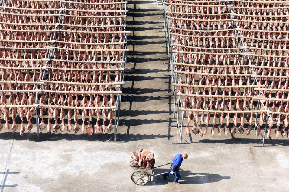Работник на заводе по производству ветчины в Цзиньхуа, Китай. 18 декабря 2017 года.