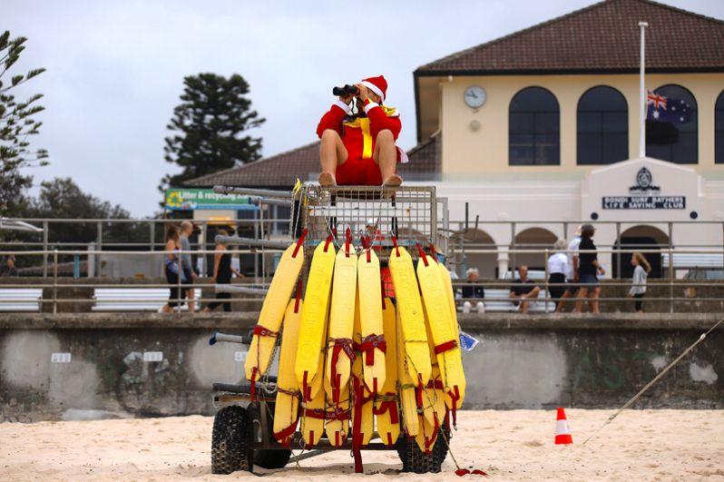 Спасатель в костюме Санта-Клауса наблюдает за отдыхающими на пляже Бонди-бич в Сиднее, Австралия.