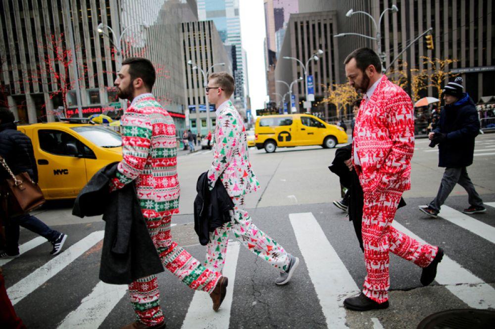 Мужчины в праздничных костюмах идут по 6-й авеню в Нью-Йорке в канун Рождества.