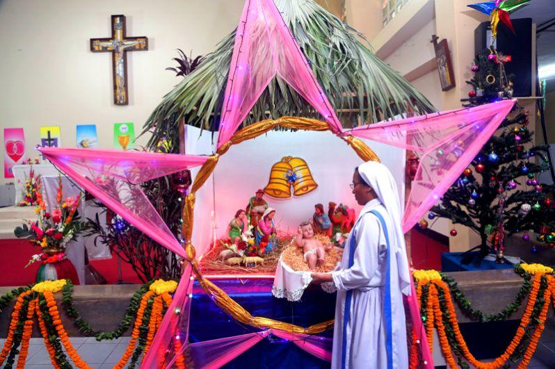 Монахиня держит фигурку младенца Иисуса в Соборе Святой Марии в Дакке, Бангладеш.