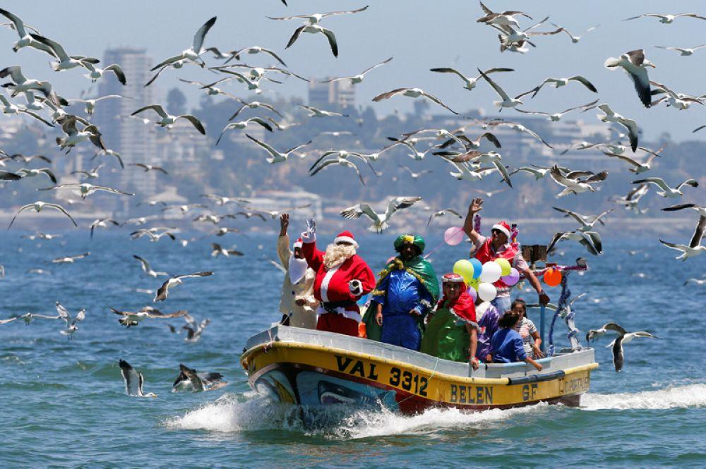 Люди в костюмах Санта-Клауса плывут в рыбацкой лодке в канун Рождества вдоль побережья Вальпараисо, Чили.