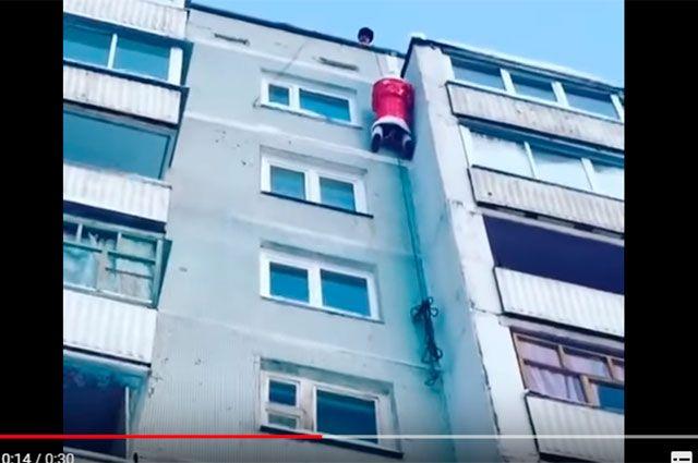 Дед Мороз спускается с крыши.