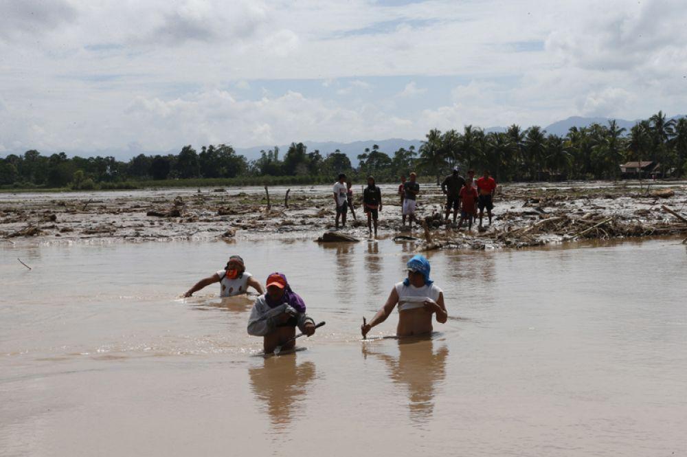 Местные жители ищут людей, пропавших без вести, в результате тайфуна, Филиппины.