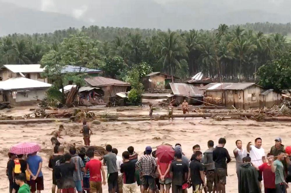 Люди пытаются спасти пострадавших от наводнения в провинции Ланао-дель-Норте, Филиппины.
