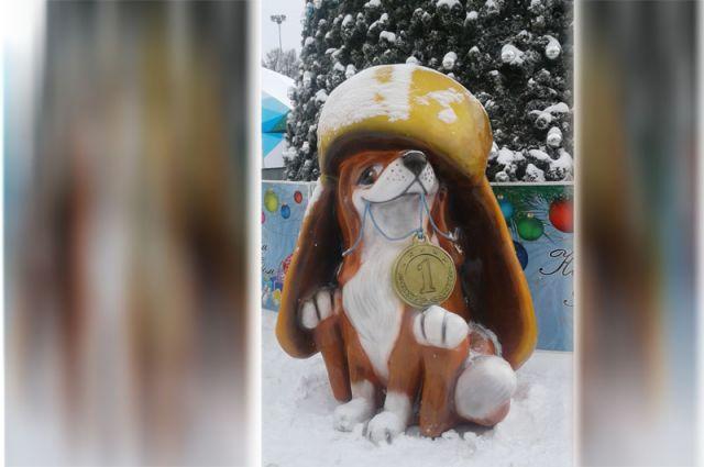 Огненного петуха сменит рыжая собака – добрый талисман. Медалька в зубах - явный намек на всероссийский форум «Россия - спортивная держава», под знаком которого должно было пройти всё новогодье. Увы, форум перенесли из-за допинг-скандалов и позиции МОК.
