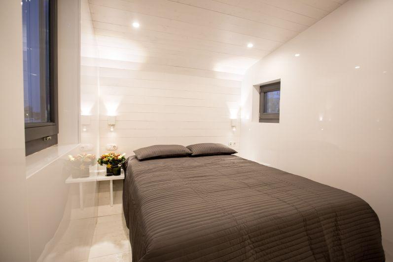 В мобильном туристическом доме площадью 19 кв. метров есть спальня с кроватью, встроенным шифоньером и столиками.