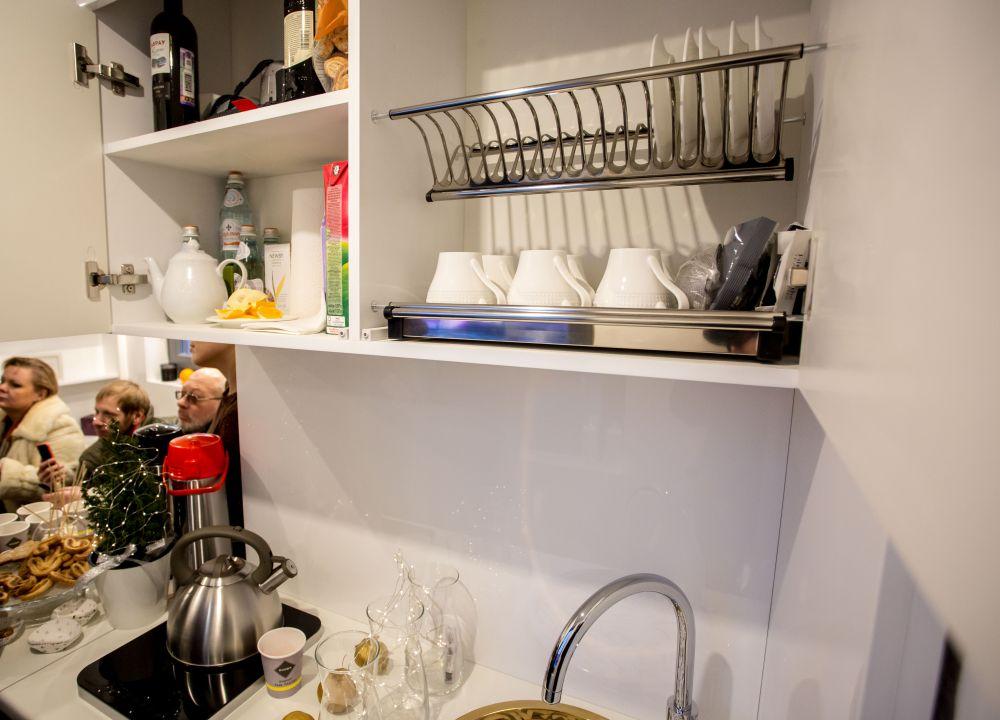 На кухне есть плита, шкафы для посуды, холодильник и раковина.