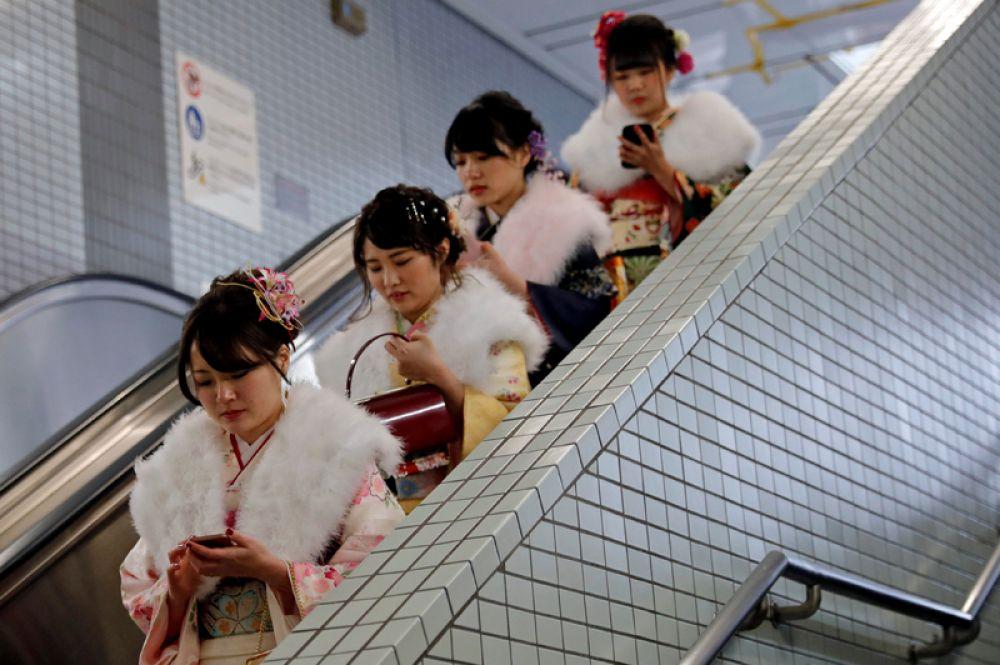 Японские девушки на эскалаторе метро после церемонии празднования Дня совершеннолетия в Токио. Каждый второй понедельник января совершеннолетие отмечают все японцы, которым со 2 апреля предыдущего года исполнилось и до 1 апреля текущего года исполнится 20 лет. 8 января 2018 года.