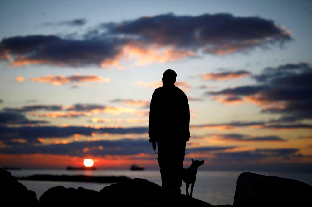 Мужчина с собакой наблюдают закат на берегу Средиземного моря в Ашкелоне, Израиль. 9 января 2018 года.