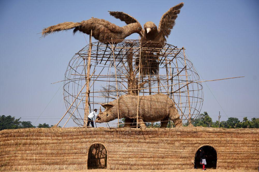 Мужчина строит фигуры из бамбука и соломы перед фестивалем Magh Bihu штате Ассам, Индия. 9 января 2018 года.