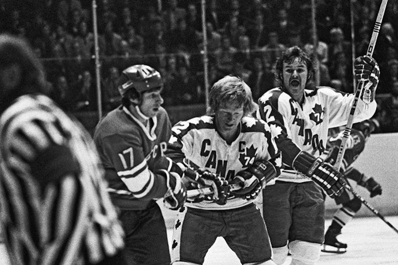 Советский хоккеист Валерий Харламов (слева) и канадский хоккеист Пэт Степелтон (в центре) в борьбе за шайбу во время матча хоккейных команд СССР и Канады. 1974 год.