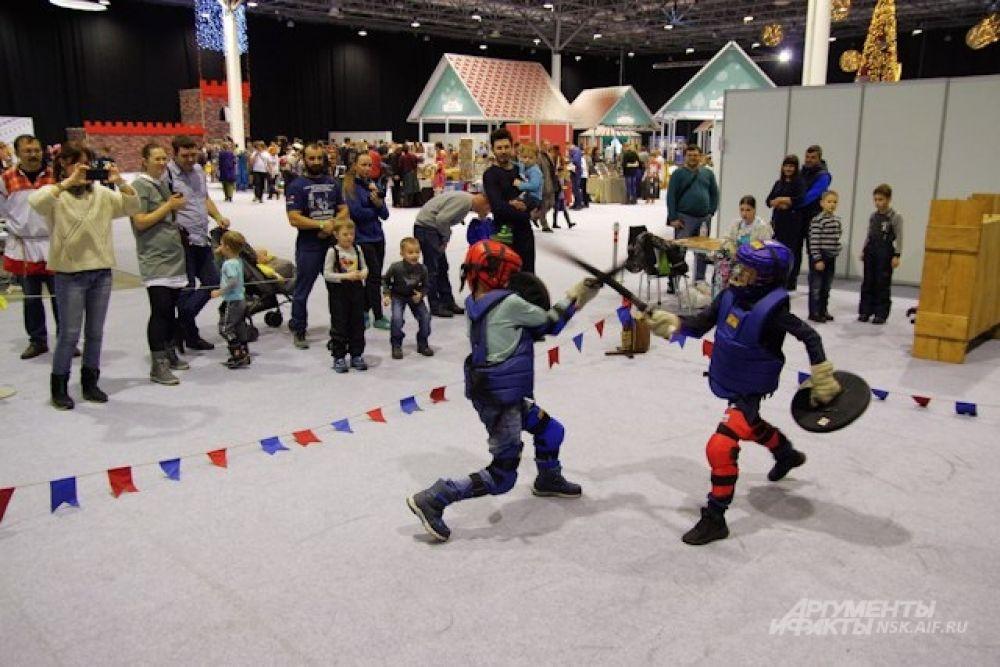 На соседней площадке молодых бойцов учили драться на мечах, оружие у юных бойцов пока учебное.