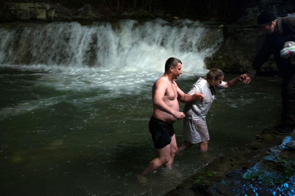 Верующие во время традиционного праздничного купания в Крещенский сочельник в водопадах реки Жане у города Геленджик в Краснодарском крае.