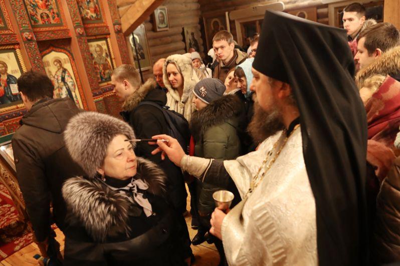 Верующие со священнослужителем во время традиционного праздничного молебна в Крещенский сочельник в Храме Святителя Николая в Измайловском Кремле в Москве.