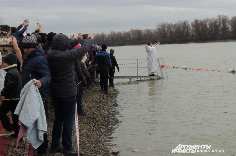 Отец Александр Игнатов освящает воду.
