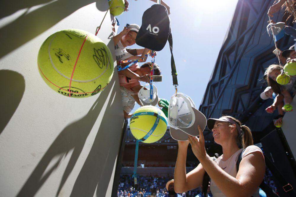 Мария Шарапова из России раздает автографы после победы над Татьяной Марией из Германии.