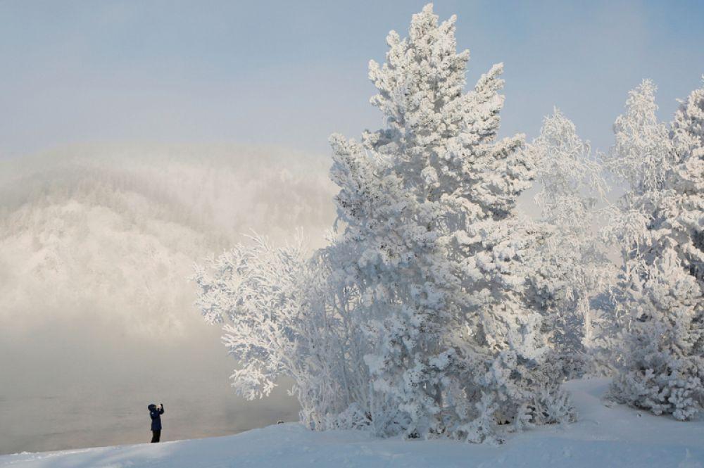 Женщина фотографирует заснеженные деревья на берегу реки Енисей, Красноярск. Температура воздуха в регионе опустилась до минус 34 градусов по Цельсию. 22 января 2018 года.