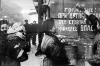 Ленинградцы закрашивают надпись об опасности при артобстреле в День снятия блокады.