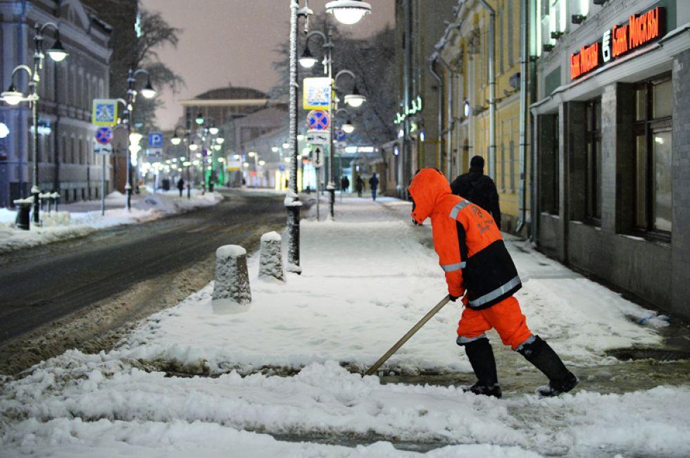 Сотрудник коммунальной службы убирает снег на улице в Москве.
