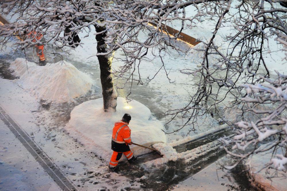 Сотрудники коммунальных служб убирают снег на улице в Москве.