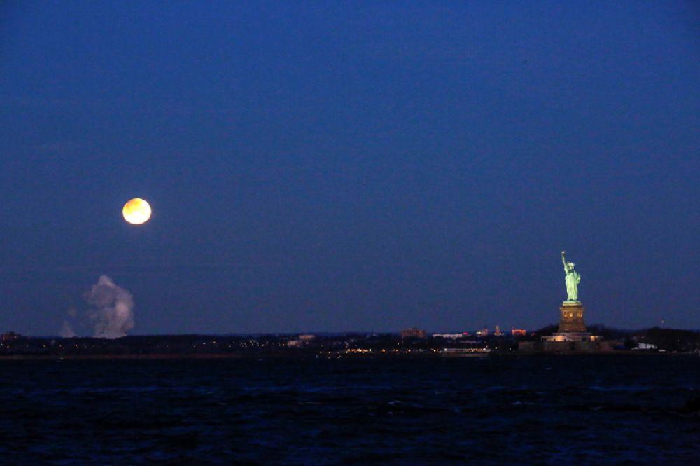 Суперлуние и статуя Свободы, вид из Бруклина, Нью-Йорк.
