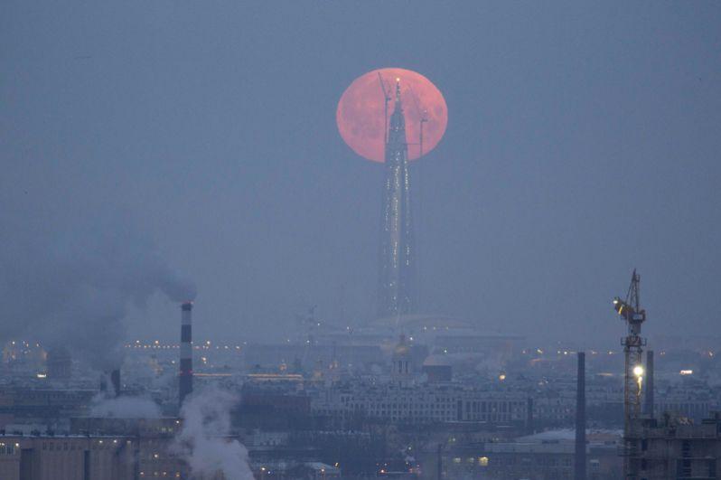 Полная луна за башней бизнес-центра «Лахта» в Санкт-Петербурге, Россия.