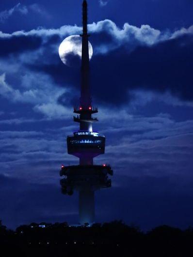 Луна над башней Telstra в Канберре, Австралия.