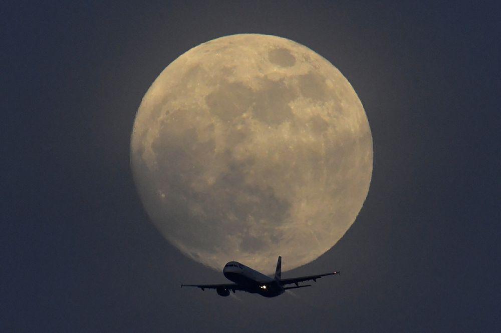 Самолет, летящий над Лондоном, на фоне полнолуния, Великобритания.