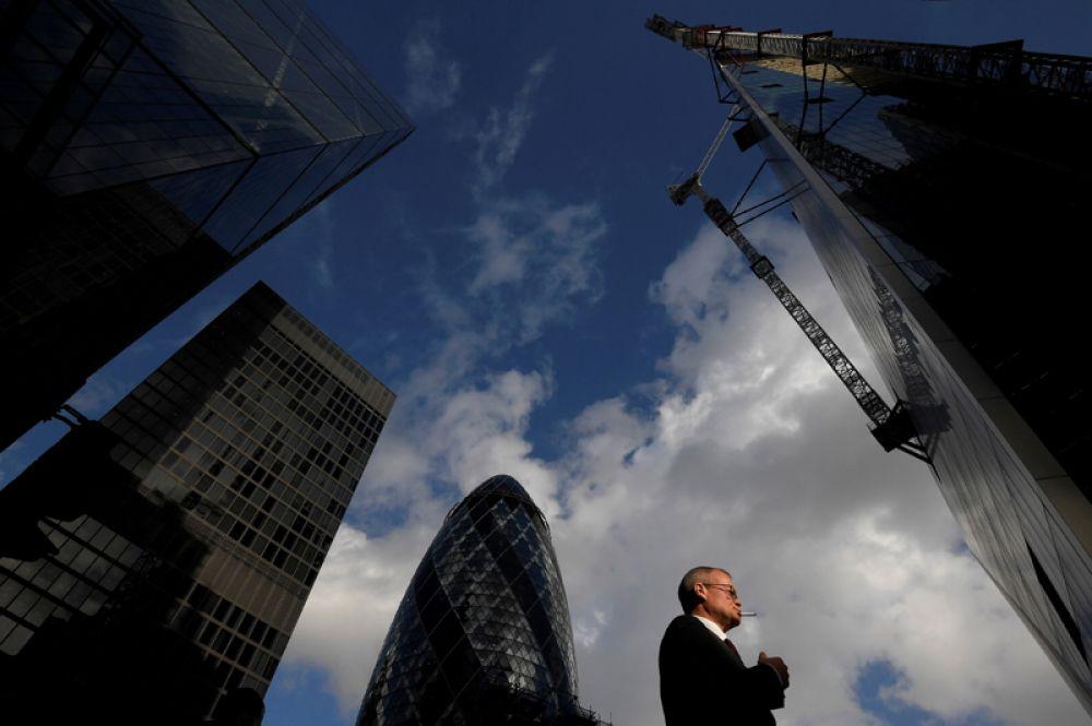 Офисный работник проходит мимо небоскребов в финансовом районе Лондона, Великобритания.