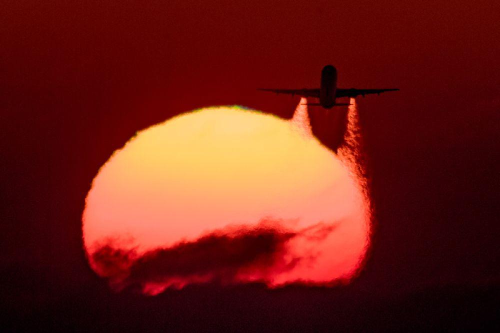 Летящий самолет Airbus A-321 на фоне заката.
