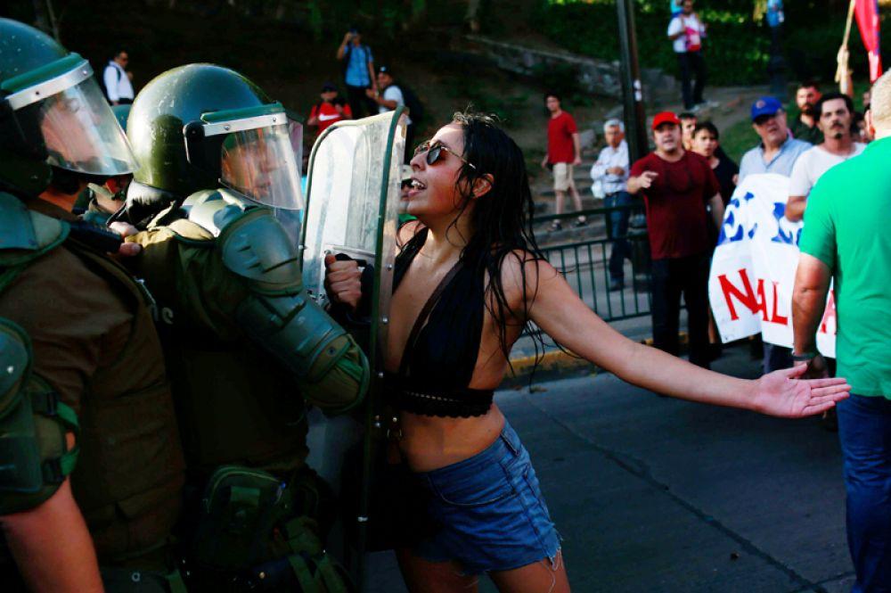 Девушка и сотрудник ОМОН во время во время митинга в Сантьяго, Чили.