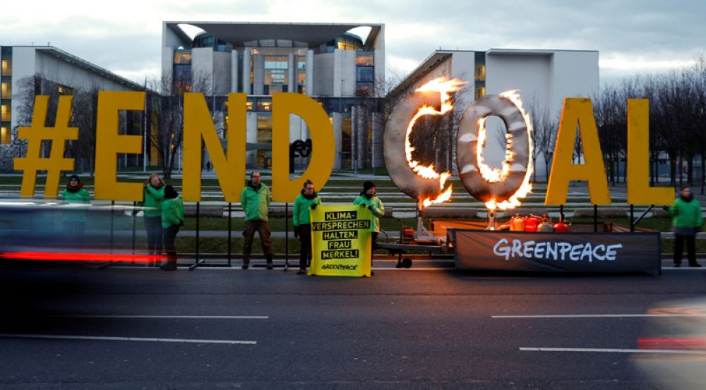 Активисты «Гринпис» протестуют против добычи каменноугольного угля перед зданием Ведомства федерального канцлера Германии в Берлине.