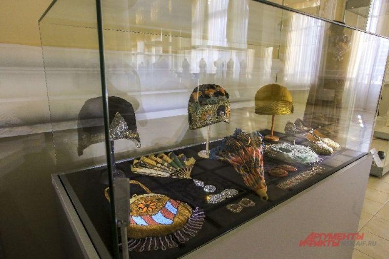 В экспозиции представлены также вышитые бисером сумочки и кокетливые веера.