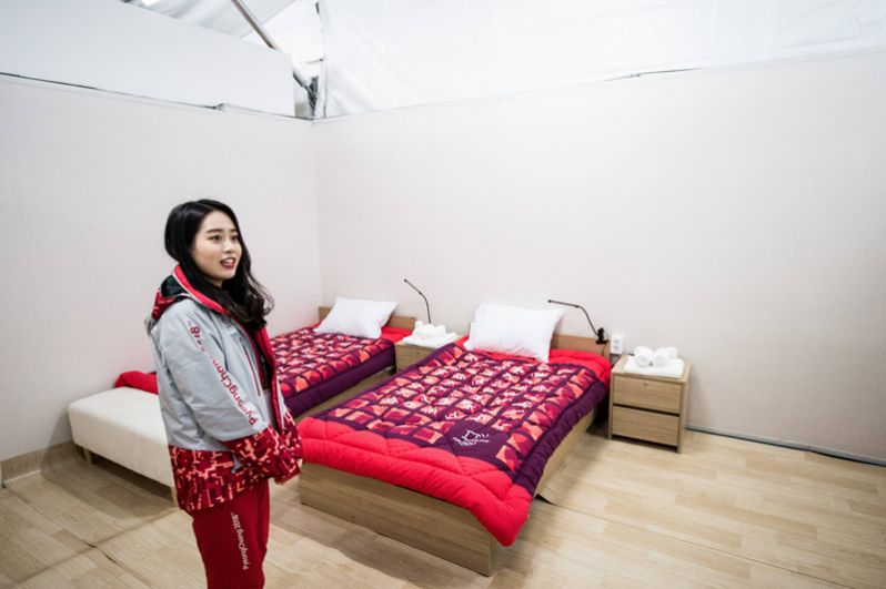 Волонтер показывает комнату для спортсменов в Олимпийской деревне.