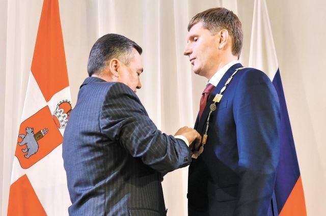 Спикер краевого Заксобрания Валерий Сухих надевает губернаторский знак на Максима Решетникова во время инаугурации 18 сентября 2017 года.