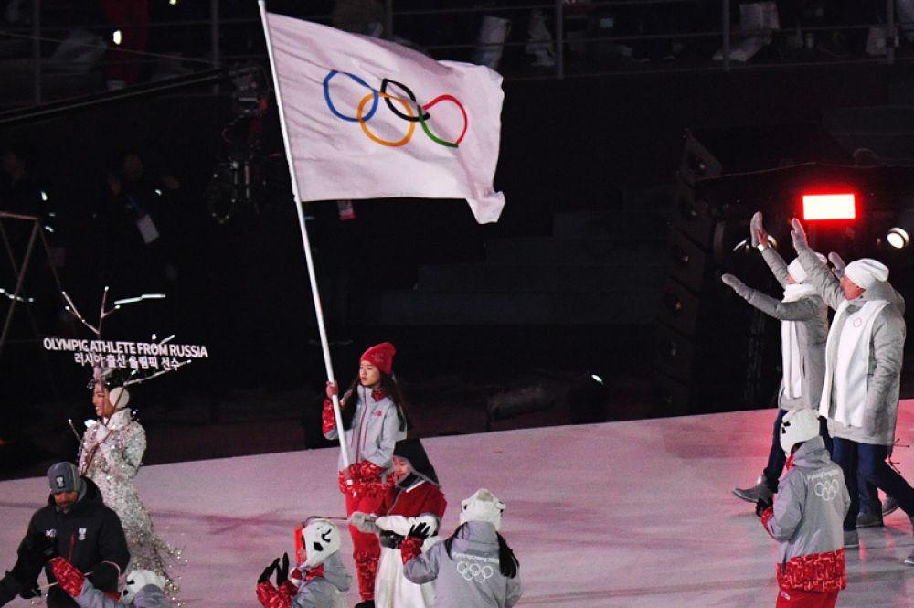 Волонтер несет олимпийский флаг, сборная России приветствуют зрителей на церемонии открытия XXIII зимних Олимпийских игр в Пхенчхане.