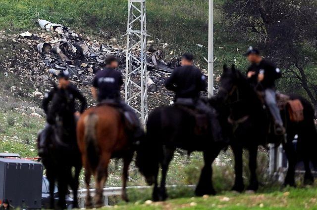Израильские силовики на фоне сбитого истребителя.