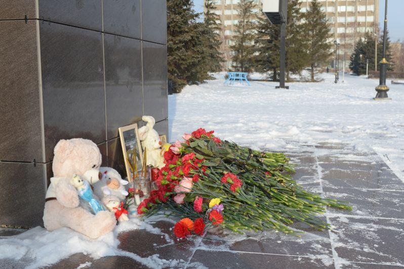 Цветы, свечи и детские игрушки у памятника Ленину в центре Орска.