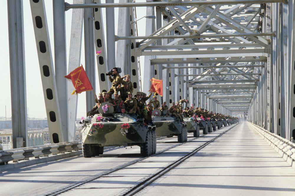 Колонна бронетехники пересекает афгано-советскую границу по мосту Дружбы через реку Амударью.