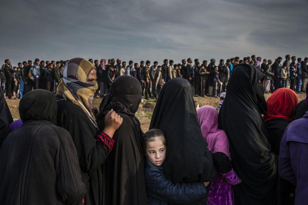Местные жители, оставшиеся в городе после битвы за Мосул, выстроились в очередь за гуманитарной помощью в районе Мамун.