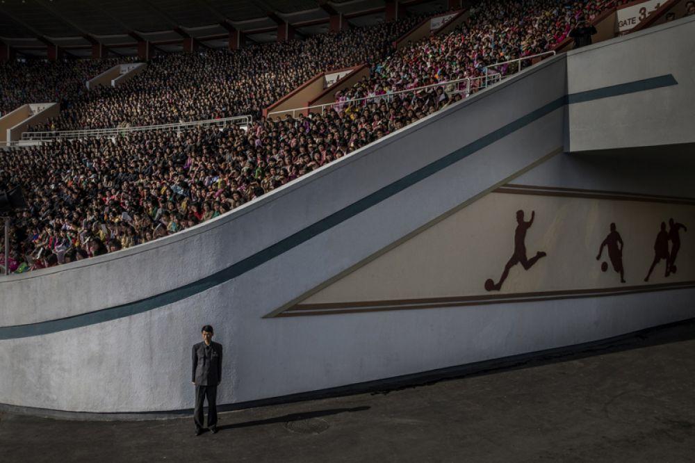 Охранник у входа на стадион имени Ким Ир Сена перед началом марафона в Пхеньяне, Северная Корея.