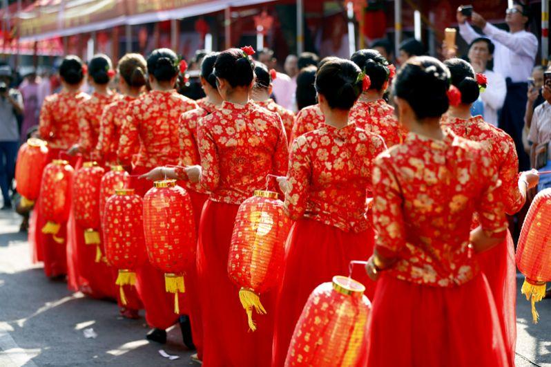 Девушки в традиционных китайских костюмах выступают во время празднования Нового года в китайском квартале Янгона, Мьянма.