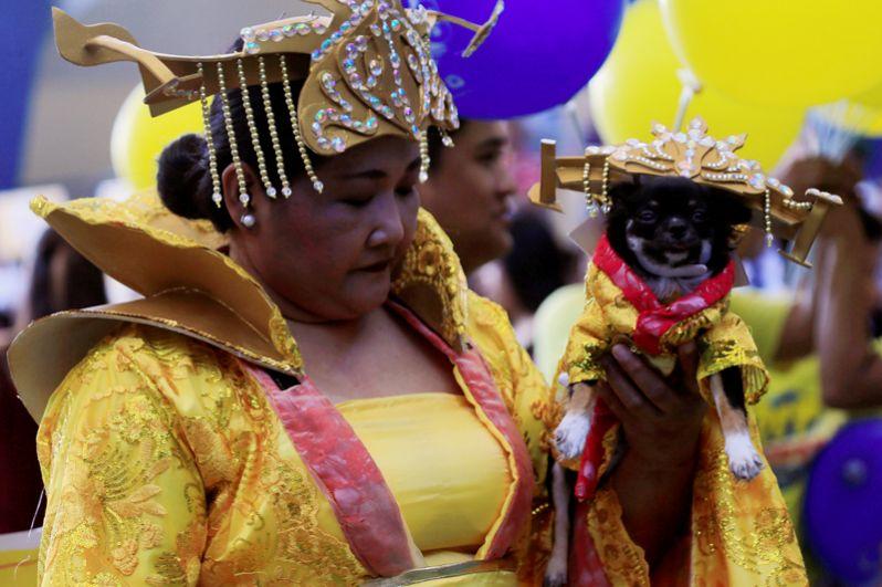 Женщина и собака в традиционных костюмах во время празднования Китайского Нового года, Манила, Филиппины.