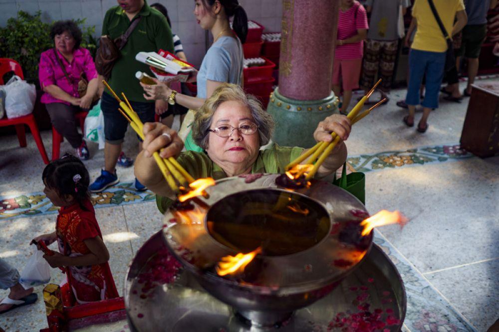 Женщина совершает обряд в одном из храмов в китайском квартале Бангкока, Таиланд.