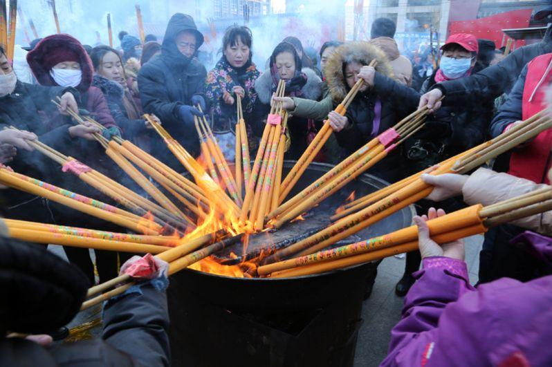 Люди зажигают ароматические палочки и молятся о счастье в храме Шишенг в первый день Нового года, Шеньян, Китай.
