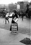 Британская суфражистка с плакатом раздает газеты или листовки на улице. Позади остановился двухъярусный автобус. Снято до 1919 года.