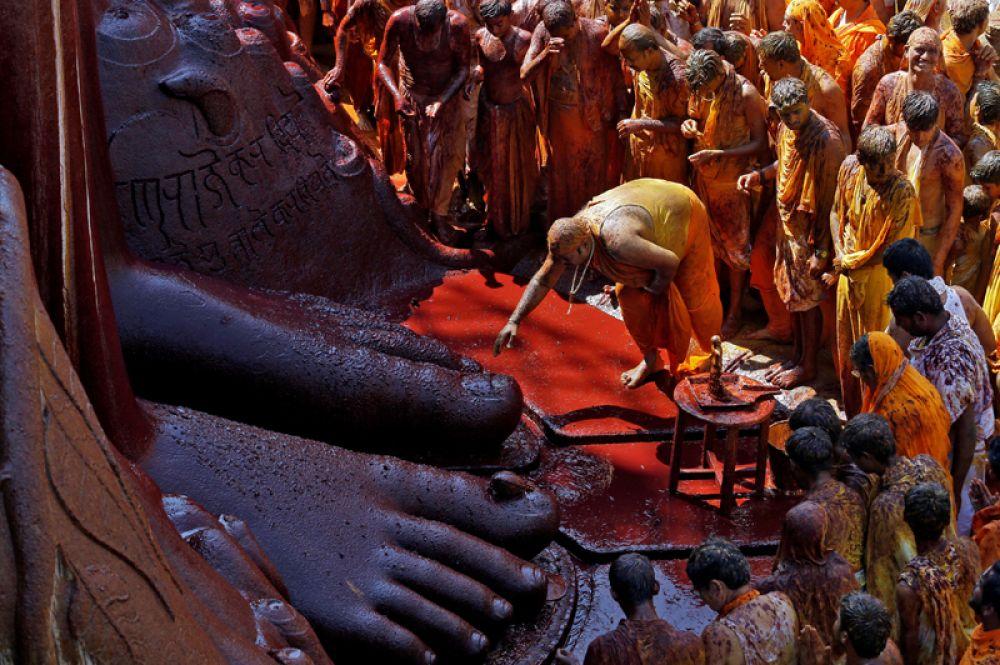 Верующий прикасается к ногам статуи бога Гомматешвары во время церемонии помазания, Шраванабелагола, Индия. Согласно джайнийскому учению, такой ритуал способствует очищению души и избавлению ее от цепи перерождений.