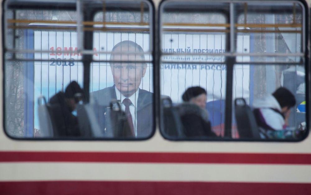 Люди едут на трамвае мимо рекламы президентской кампании Владимира Путина перед предстоящими выборами, Санкт-Петербург, Россия.