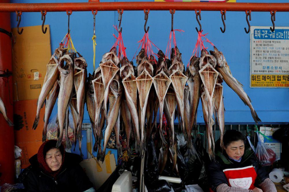 Уличные торговцы сушеной рыбой на местном рынке в Канныне, Южная Корея, где проходят Олимпийские игры.